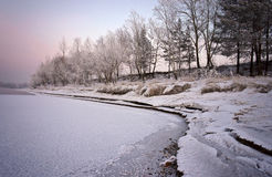 Bank of the river, covered with snow and light conditions, the setting sun Stock Photo