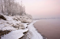 Bank of the river, covered with snow and light conditions, the setting sun Royalty Free Stock Photos