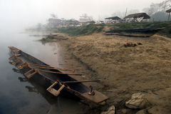 On the bank of the river near the edge of the water there is a large Nepalese wooden canoe boat, inside the chairs and oars, in th. E background in the fog are Royalty Free Stock Photography