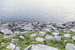 Bank of a river with stones Stock Images