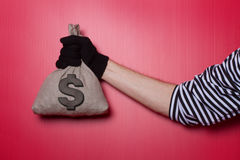Bank Robber Hand Whit Money Bag. Money bag with dollar sign on red background Royalty Free Stock Photography