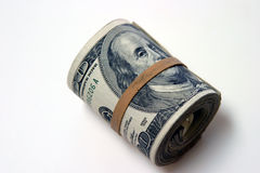 Bank roll isolated on white. A rather thick bank roll of $100.00 bills secured with a rubber band stock photo