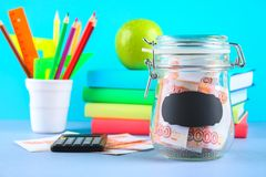 Bank with Russian money, 5000 rubles and a calculator, books on a gray background. Finance, moneybox, education. Bank with Russian money, 5000 rubles and a Royalty Free Stock Photo