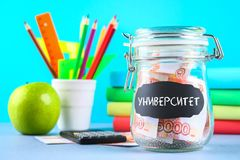 Bank with Russian money, 5000 rubles and a calculator, books on a gray background. Finance, moneybox, education. Text in Russian:. University Royalty Free Stock Photos