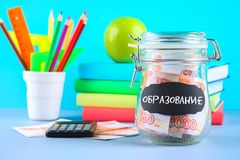 Bank with Russian money, 5000 rubles and a calculator, books on a gray background. Finance, moneybox. Text in Russian: education. Bank with Russian money, 5000 Royalty Free Stock Photos