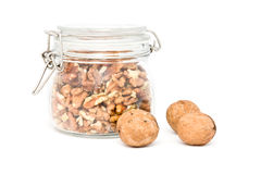 Bank with shelled walnuts and three whole walnuts. Bank with shelled walnuts and three whole walnuts Stock Images