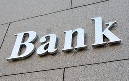Bank sign. Shiny metallic bank sign on stone wall stock photo