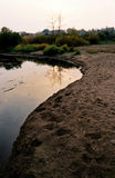 Bank of the small river. At sunset Royalty Free Stock Images