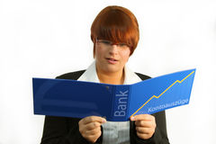 Bank statement. Young woman looking shocked at statement of account Stock Image