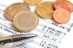 Bank Statement. Euro coins and ball pen on top of a bank statement Stock Image