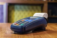 Bank terminal with a printed check and colored buttons standing royalty free stock photos