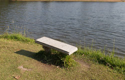 Bank am Ufer des Teichs Stockbild