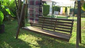 Bank Uitstekende en houten schommeling die in park slingeren Motielengte van het slingeren van stoel stock videobeelden