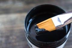 Bank und Bürste mit schwarzer Acrylfarbe Lizenzfreie Stockfotografie