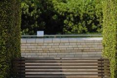 Bank und Büsche im Park lizenzfreie stockfotos