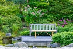 Bank und Blumen im Park Lizenzfreie Stockfotos