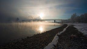 Bank van de rivier en de brug in de mist Stock Foto