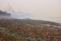 Bank van Yamuna-rivier met huisvuil en Taj Mahal in een mist wordt behandeld die stock afbeeldingen