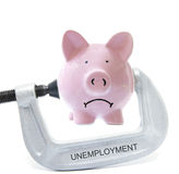 Bank vice. Sad piggy bank being squeezed in Unemployment vice, on white Royalty Free Stock Photos