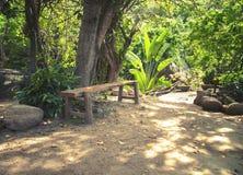 Bank voor een rust in een park in de wildernis Stock Foto's