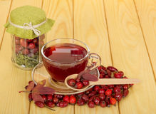 Bank with wild rose and cup  tea on  light wood. Royalty Free Stock Image