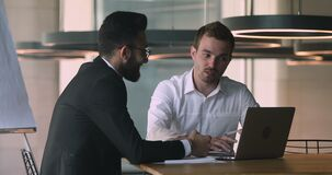 Bank worker explaining deal benefits to focused arabic businessman.