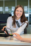 Bank worker offer to pay by credit card. In bank Royalty Free Stock Photos