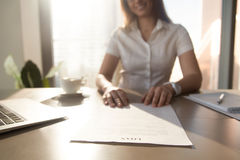 Bank worker offering loan agreement, focus on document, close up. Bank worker offering to read terms of business loan agreement for home purchase, female Royalty Free Stock Photo