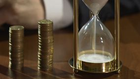 Bank worker turning hourglass on table, business projects income, running time stock video