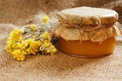 Bank z miodem z kolorów żółtych suchymi kwiatami na burlap Boczny widok Obraz Royalty Free