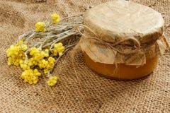 Bank z miodem z kolorów żółtych suchymi kwiatami na burlap Boczny widok Zdjęcia Royalty Free