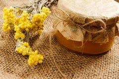 Bank z miodem z kolorów żółtych suchymi kwiatami na burlap Boczny widok Fotografia Stock