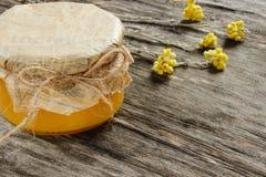 Bank z miodem z kolorów żółtych suchymi kwiatami na szarym drewnianym tle Boczny widok Zdjęcia Stock
