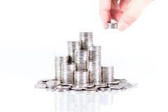banka pieniądze prosiątka kładzenia oszczędzanie żeńska prawa ręka kładzenie monety sterta Fotografia Royalty Free