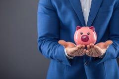 banka pieniądze prosiątka kładzenia oszczędzanie Biznesmena mienia menchii prosiątko i kładzenie moneta w prosiątko banka Obrazy Stock