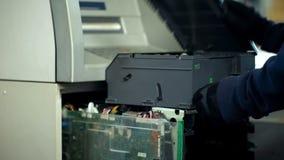 Bankanställd som öppnar säker ATM och att kontrollera sammanbrottet, kassa-i-transport service arkivfoto