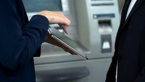 Bankassistenzhelfender Kunde, zum von Bahnkarten unter Verwendung der Tablette, Rechnungszahlung zu buchen lizenzfreie stockfotos