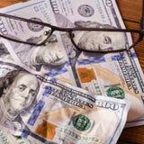 Bankbiljet drie van Honderd Amerikaanse dollars en glazen op de houten bedelaars stock foto