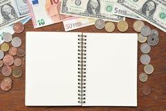 Bankbiljet en muntstukken met notitieboekje Stock Foto
