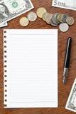 Bankbiljet en muntstukken met notitieboekje Stock Afbeelding