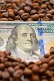 Bankbiljet van 100 Amerikaanse dollars, tussen korrels van koffie Bedrijfsconcept voor de aankoop, de verkoop, de levering en de  stock afbeeldingen