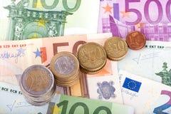 Bankbiljetten en euro muntstukken Stock Foto's