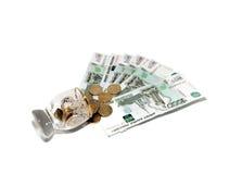 Bankbiljetten, muntstukken en een glas Royalty-vrije Stock Fotografie