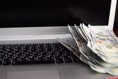 Bankbiljetten over laptop het geld van toetsenborddollars Stock Fotografie