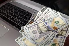 Bankbiljetten over laptop het geld van toetsenborddollars Stock Afbeeldingen