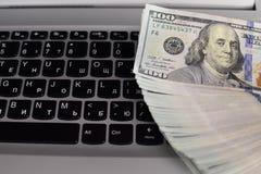 Bankbiljetten over laptop het geld van toetsenborddollars Royalty-vrije Stock Afbeeldingen