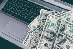 Bankbiljetten over laptop het geld van toetsenborddollars Stock Foto's