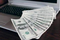 Bankbiljetten over laptop het geld van toetsenborddollars Royalty-vrije Stock Foto's