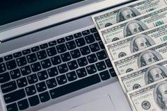 Bankbiljetten over laptop het geld van toetsenborddollars Stock Foto