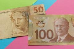 Bankbiljetten van Canadese munt: Dollar en Braziliaanse Munt: Echt Rekeningen op kleurrijke heldere lijst